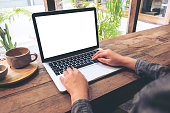 Mockup image of hands using laptop with blank white screen on vintage wooden table in cafe