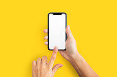 Mockup of female hands touching cell phone with blank screen on yellow background.