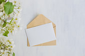 Mockup white greeting card and envelope with white spring flowers and light background