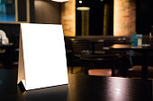 Mockup empty white label menu frame on table with cafe restaurant interior background