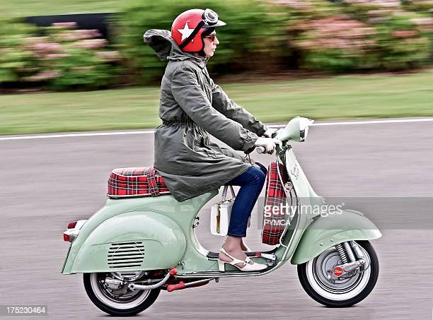 A mod girl wearing a red helmet riding her scooter on the street UK 2010