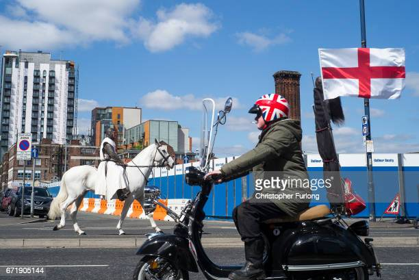 A mod rides his scooter past a man dressed as Saint George leading the Manchester St George's Day parade on April 23 2017 in Manchester England...