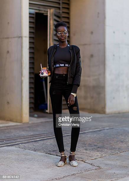 Model Mary Akech wearing a black bomber jacket cropped shirt black ripped denim jeans and laced flats outside Bec Bridge at MercedesBenz Fashion Week...