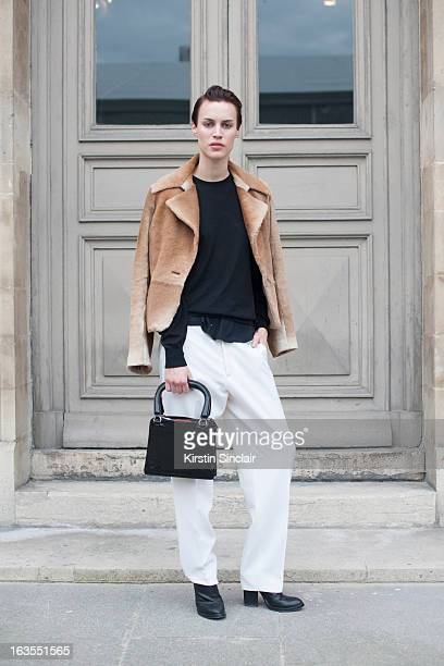 Model Alana Bunte wears Black Denim trousers Versace sweater Max Mara jacket Miu Miu bag and Haider Ackermann shoes on day 7 of Paris Womens Fashion...