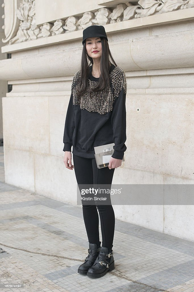 Model Amalie Gassmann wears Jeffrey Campbell boots, H and M top, Addicted hat and a Zara clutch bag on day 2 of Paris Womens Fashion Week Autumn/Winter 2013 on March 1, 2013 in Paris, France.