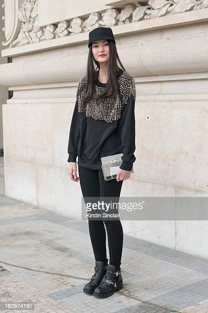 Model Amalie Gassmann wears Jeffrey Campbell boots H and M top Addicted hat and a Zara clutch bag on day 2 of Paris Womens Fashion Week Autumn/Winter...