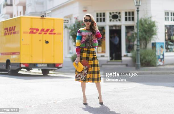 Model and Blogger Alexandra Lapp in front of DHL van wearing a yellow and red pleated tartan skirt embroidered with a spaniel dog and belt buckle...