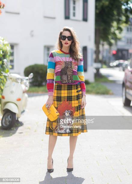 Model and Blogger Alexandra Lapp wearing a yellow and red pleated tartan skirt embroidered with a spaniel dog and belt buckle closure colorful...