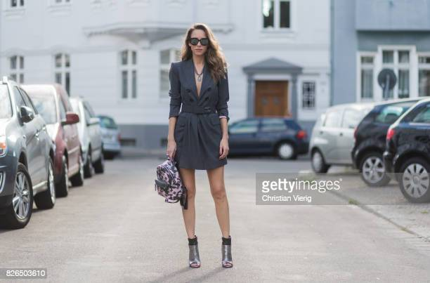 Model and fashion blogger Alexandra Lapp wearing a blazer dress in grey by Dsquared with matching waist belt Chanel broach camouflage Stark backpack...
