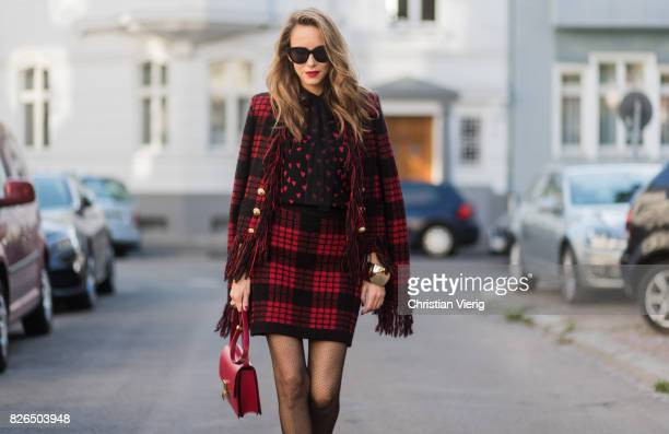 Model and fashion blogger Alexandra Lapp wearing a military jacket in red and black with checkered pattern and frayed sleeves from Balmain plaid...