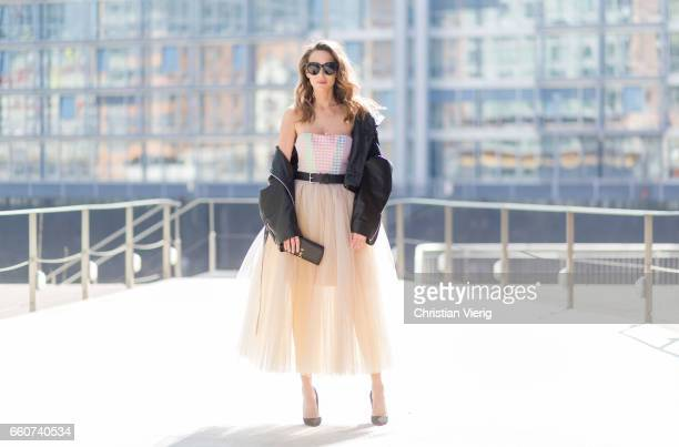 Model and fashion blogger Alexandra Lapp wearing a multicolored sleeveless brocade tulle dress from Natasha Zinko a black biker leather jacket with...