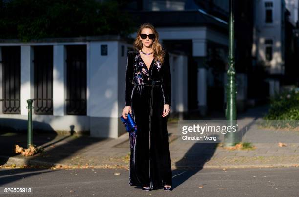 Model and fashion blogger Alexandra Lapp wearing a V neck velvet jumpsuit from Vivetta with a cord belt blue metallic lacquer Boy bag by Chanel...