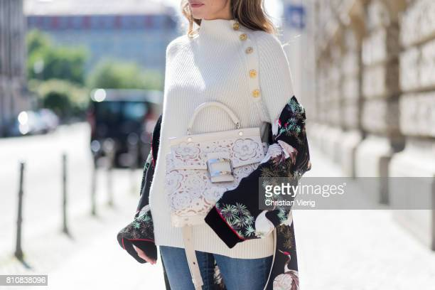 Model and fashion blogger Alexandra Lapp wearing white leather tassel mules from Santoni a off white cashmere pullover by Heartbreaker Kimono with...