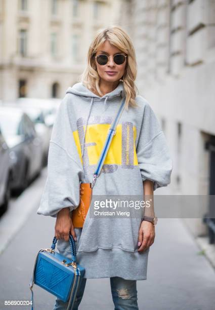 Model and fashion blogger Gitta Banko wearing a grey oversize cotton sweater with yellow and glittery silver print by Marina Hoermanseder Cora jeans...