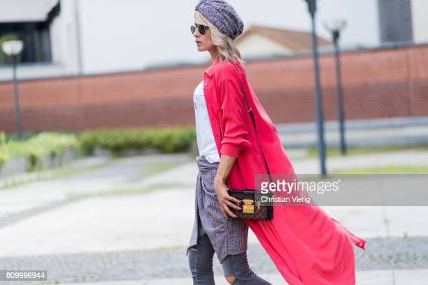 Model and fashion blogger Gitta Banko wearing a hibiscuscolored stretchy silk dress as a coat by Jadicted lightgrey jeans in destroyed look from...