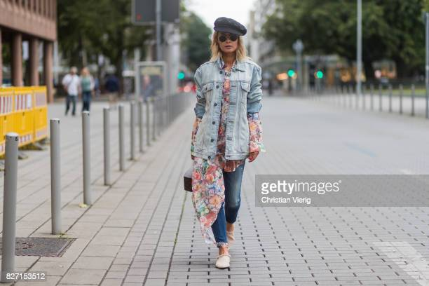 Model and fashion blogger Gitta Banko wearing a long cotton floralpatterned blouse by MM6 Maison Margiela jeans jacket with handpainted Matryoshka...