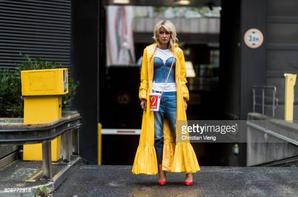 Model and fashion blogger Gitta Banko wearing a long yellow patentleather coat by Marina Hoermanseder a white tshirt by James Perse under a demin...
