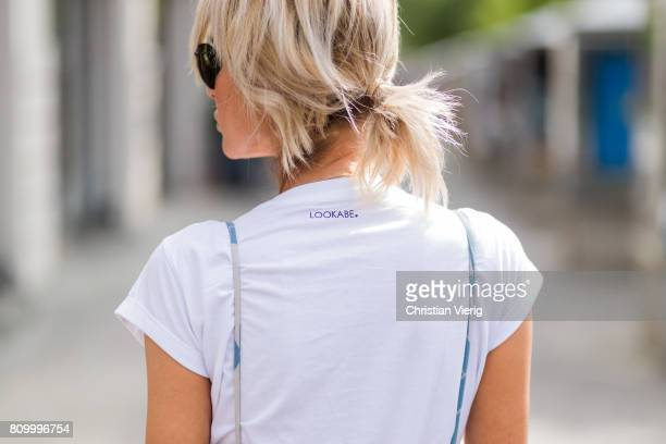 Model and fashion blogger Gitta Banko wearing a white organiccotton statement tshirt from the LOOKABE x BLONDWALK collection underneath a silk with...