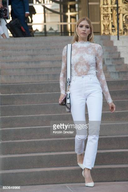 Model and Socialite Lena Perminova wears a white lace top and white jeans and shoes with a Dior bag day 2 of Paris Haute Couture Fashion Week...
