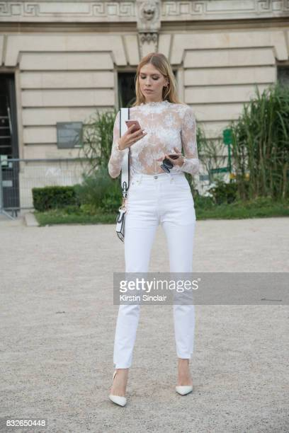 Model and Socialite Lena Perminova wears a white lace top with white jeans and shoes and a Dior bag day 2 of Paris Haute Couture Fashion Week...