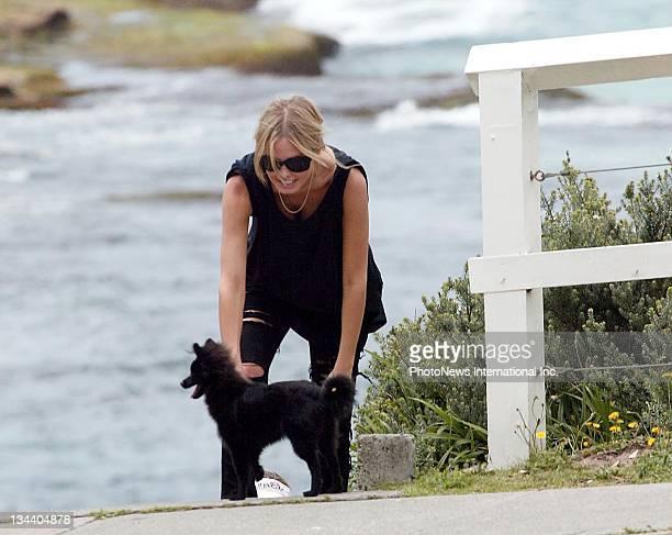 Model and TV personality Lara Bingle and friend walk her dog on Tamarama Beach on December 6 2008 in Sydney Australia
