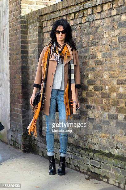 Model Ashleigh Good exits the Burberry Prorsum show in a Burberry scarf and trench coat during London Fashion Week Fall/Winter 2015/16 at Kensington...