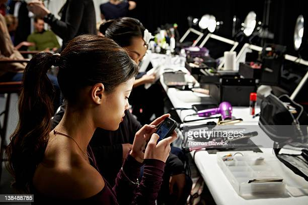 Model backstage at fashion show looking at phone