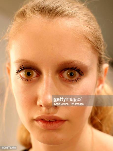 A model backstage wearing yellow contact lenses at the Aminaka Wilmont Autumn/Winter 2011 show at London Fashion Week