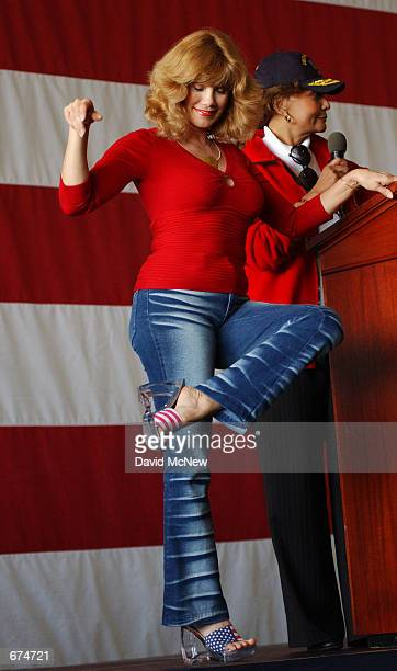 Model Barbie Benton shows off her stars and stripes shoes aboard the USS Bonhomme Richard November 30 2001 at the 32nd Street Naval Station in San...