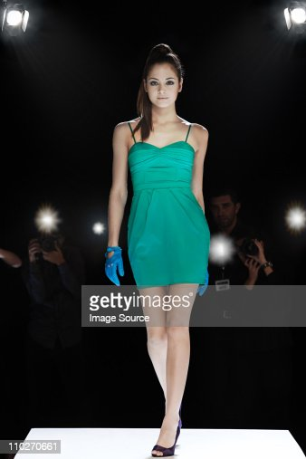 Model being photographed on catwalk at fashion show