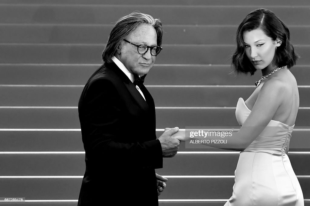 US model Bella Hadid (R) and her father Mohamed Hadid pose as they arrive on May 17, 2017 for the screening of the film 'Ismael's Ghosts' (Les Fantomes d'Ismael) during the opening ceremony of the 70th edition of the Cannes Film Festival in Cannes, southern France. / AFP PHOTO / Alberto PIZZOLI