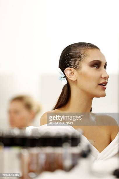 US model Bella Hadid is reflected in a mirror after having her makeup applied in a backstage area ahead of the Christian Dior Cruise fashion show at...