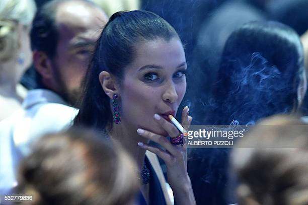 US model Bella Hadid smokes a cigarette during the amfAR's 23rd Cinema Against AIDS Gala on May 19 2016 at the Hotel du CapEdenRoc in Cap d'Antibes...