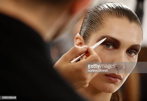 US model Bella Hadid waits as a makeup artist applies finishing touches to her eyebrow backstage ahead of the Christian Dior Cruise fashion show at...