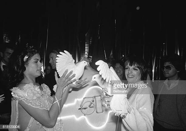 Model Bianca Jagger and singer Liza Minnelli holding white doves at the popular nightclub Studio 54