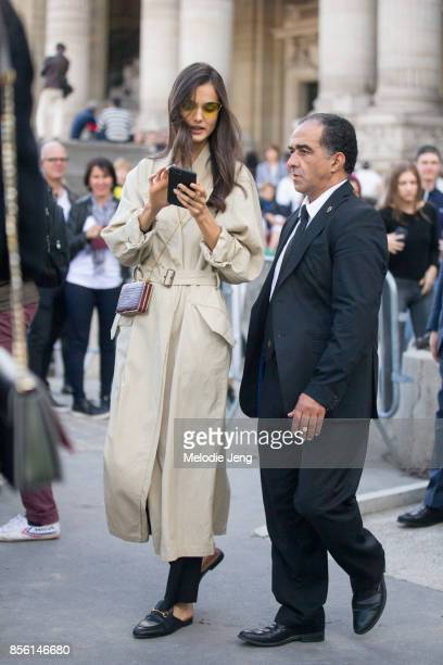 Model Blanca Padilla wears a tan trench coat outside the Elie Saab show on September 30 2017 in Paris France