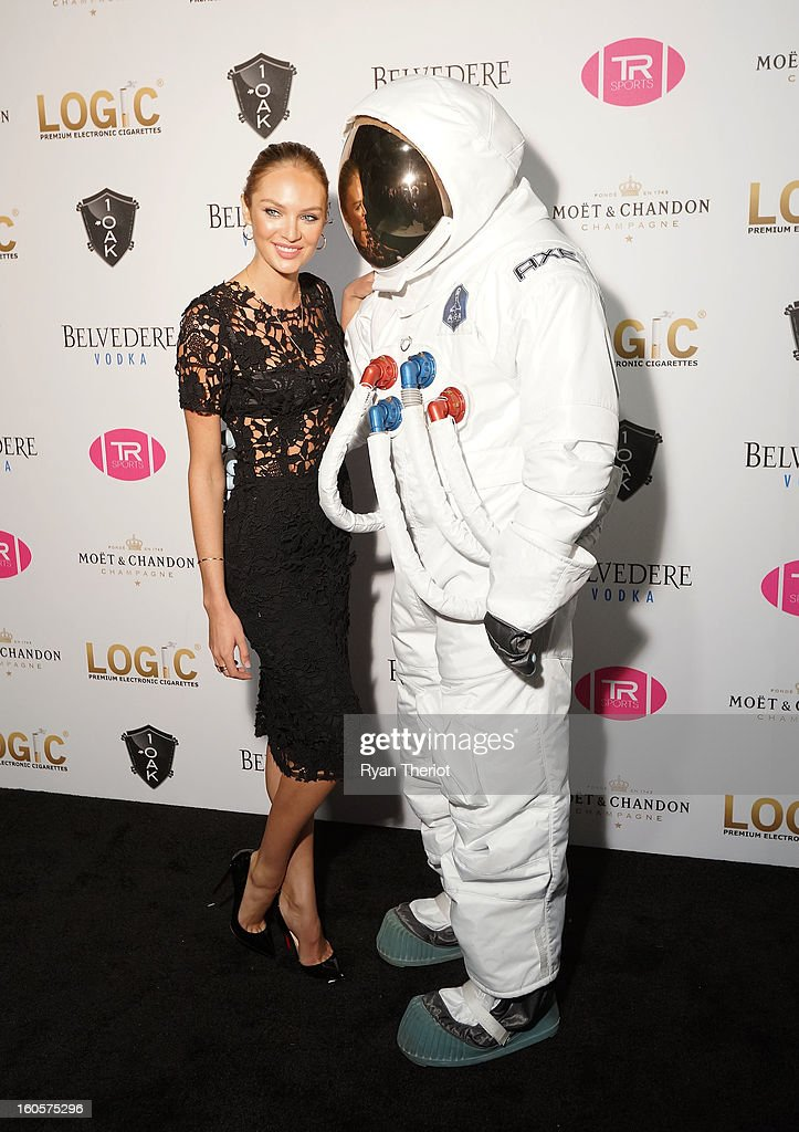 Model Candice Swanepoel poses with an AXE astronaut at 1 OAK New Orleans Presented By LOGIC Electronic Cigarettes at Jax Brewery on February 2, 2013 in New Orleans, Louisiana.