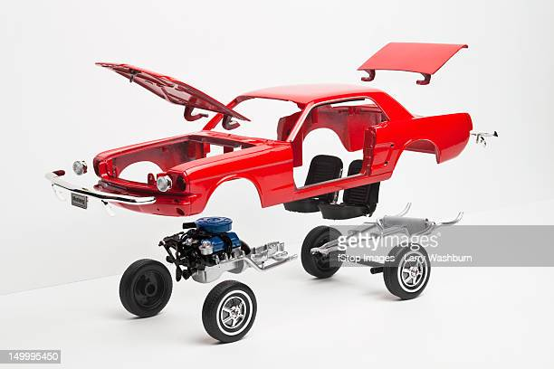 A model car taking a part, some pieces in mid-air