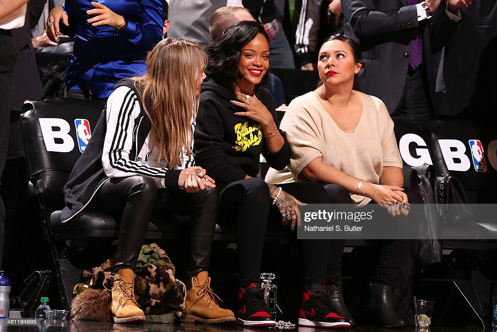 Model Cara Delevingne and artist Rihanna and her friend watch the Brooklyn Nets play the Atlanta Hawks at the Barclays Center on January 6, 2014 in the Brooklyn borough of New York City.