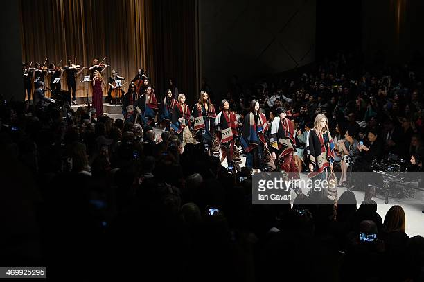 Model Cara Delevingne leads the finale on the the runway at Burberry Womenswear Autumn/Winter 2014 at Kensington Gardens on February 17 2014 in...