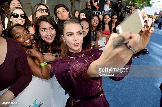 Model Cara Delevingne takes a selfie with fans at the 2015 MTV Movie Awards at Nokia Theatre LA Live on April 12 2015 in Los Angeles California