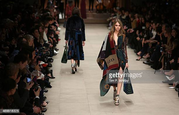 Model Cara Delevingne walks the runway at the Burberry Prorsum show at London Fashion Week AW14 at Perks Fields Kensington Gardens on February 17...