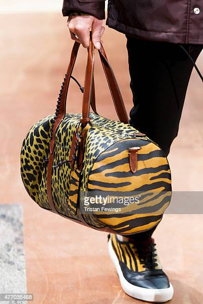 A model carries a bag on the runway at the Coach show during The London Collections Men SS16 at Lindney Hall on June 13 2015 in London England