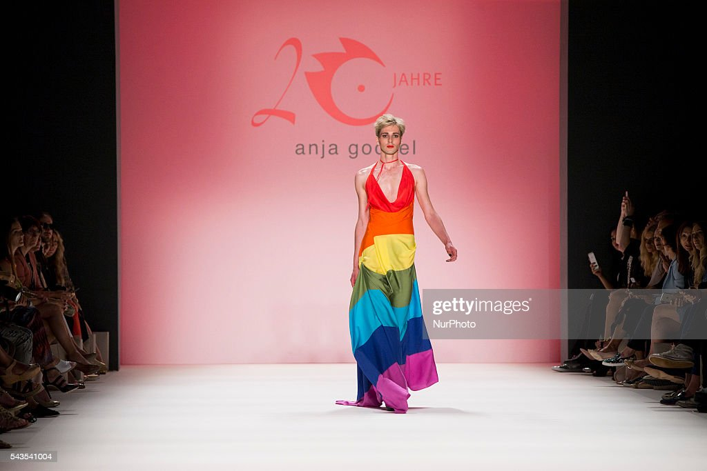 A model carries a LGBT rainbow flag as he walks the runway at the Anja Gockel show during the Mercedes-Benz Fashion Week Berlin Spring / Summer 2017 at Erika Hess Eisstadion in Berlin, Germany on June 29, 2016.