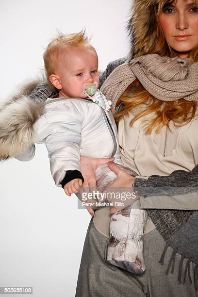 A model carrying a baby walks the runway at the Sportalm show during the MercedesBenz Fashion Week Berlin Autumn/Winter 2016 at Brandenburg Gate on...