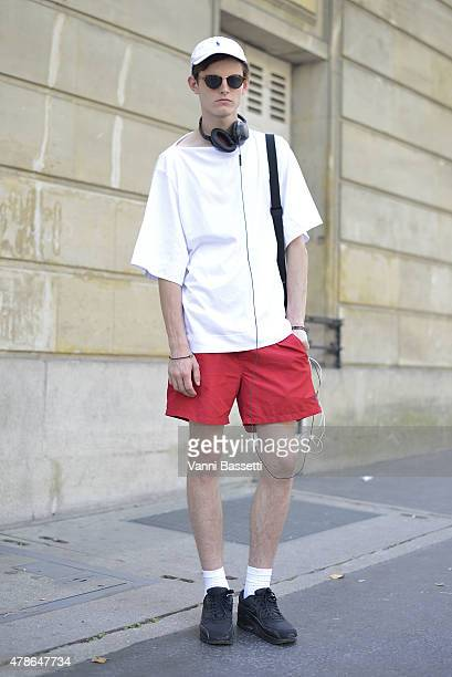 Model Charlie Adshead poses wearing a Juun J tshirt Polo Ralph Laurent shorts and cap and Nike shoes on June 26 2015 in Paris France