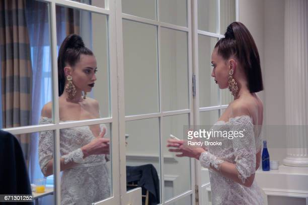 A model checks out her cell phone backstage at the Berta Runway show during New York Fashion Week Bridal April 2017 at The Plaza Hotel on April 21...
