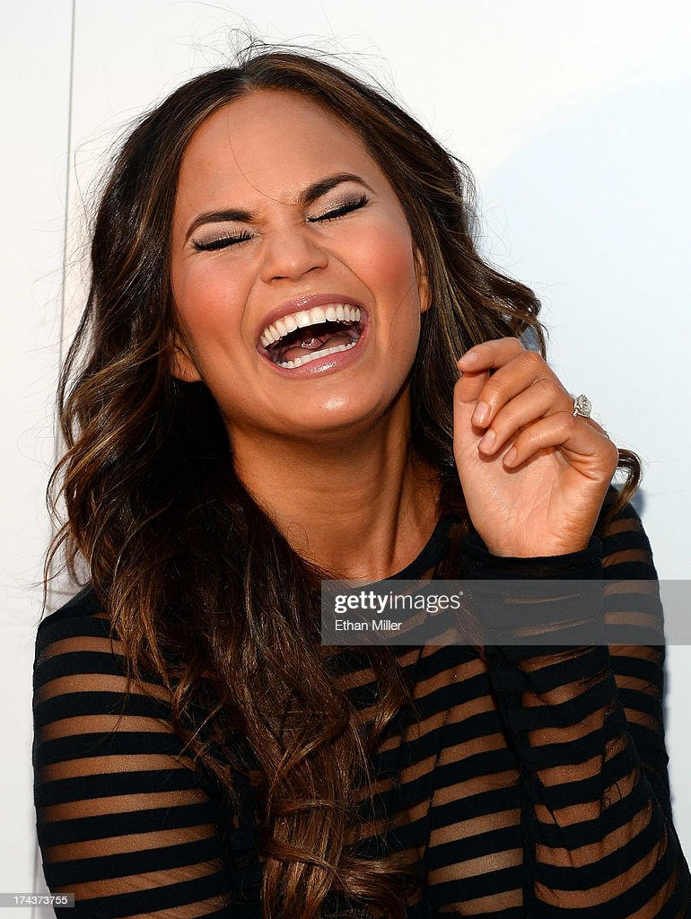Model Chrissy Teigen laughs as she arrives at Vegas Magazine's summer issue party at the Azure Luxury Pool at The Palazzo Las Vegas on July 24, 2013 in Las Vegas, Nevada.