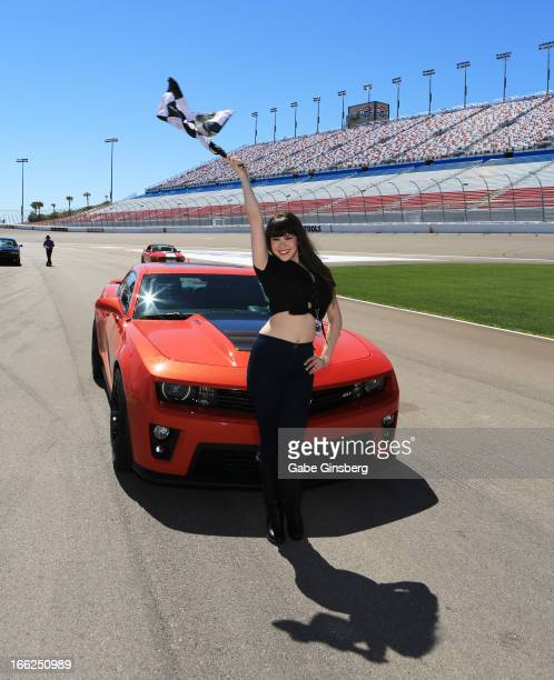 Model Claire Sinclair from the show 'Pin Up' poses with a checkered flag in front of a Chevrolet Camaro ZL1 at the American Muscle Car Challenge by...