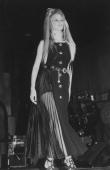 Model Claudia Schiffer wearing a Gianni Versace dress on the runway at the benefit he threw for AMFAR